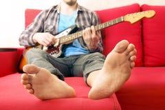Giovane con indifferenza vestito con la chitarra che gioca le canzoni nella stanza a casa Concetto online di lezioni della chitar immagine stock libera da diritti