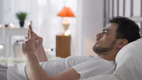 Giovane con Internet di lettura rapida del telefono in camera da letto archivi video