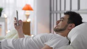 Giovane con Internet di lettura rapida del telefono in camera da letto stock footage