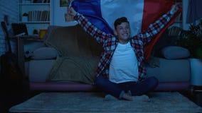 Giovane con la bandiera francese che incoraggia la casa favorita della squadra di football americano, evento di sport archivi video