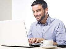 Giovane con la barba che lavora al computer portatile Fotografie Stock