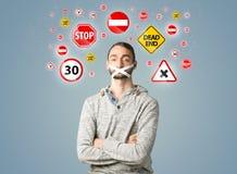 Giovane con la bocca ed i segnali stradali incollati Fotografia Stock