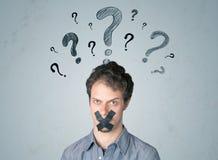 Giovane con la bocca incollata ed i simboli del punto interrogativo Fotografia Stock