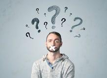 Giovane con la bocca incollata ed i simboli del punto interrogativo Immagini Stock Libere da Diritti