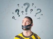 Giovane con la bocca incollata ed i simboli del punto interrogativo Immagine Stock Libera da Diritti