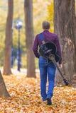 Giovane con la chitarra che cammina nel parco Immagini Stock Libere da Diritti