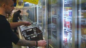 Giovane con la latteria d'acquisto del carrello o drogherie refrigerate al supermercato nella sezione refrigerata archivi video