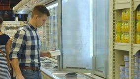 Giovane con la latteria d'acquisto del carrello o drogherie refrigerate al supermercato nella sezione refrigerata stock footage