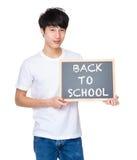 Giovane con la lavagna che mostra di nuovo al messaggio della scuola Fotografia Stock Libera da Diritti