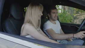 Giovane con la ragazza che usando cruscotto sensoriale dentro l'auto moderna stock footage