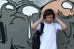 Giovane con le cuffie che ascolta la musica Immagine Stock