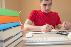 Giovane con le fatture ed il calcolatore a casa Lo studente che si siede fra i libri e calcola Immagine Stock