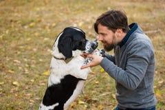Giovane con le passeggiate del cane nel parco di autunno immagini stock libere da diritti