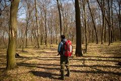 Giovane con lo zaino che fa un'escursione nella natura della foresta e nel concetto di esercizio fisico immagini stock