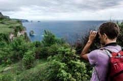 Giovane con lo zaino sulla collina che fa una foto del paesaggio scenico Fotografia Stock Libera da Diritti
