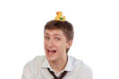 Giovane con un'anatra di gomma sulla sua testa Fotografia Stock