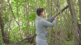 Giovane con un'ascia che taglia gli alberi a pezzi nella foresta video d archivio