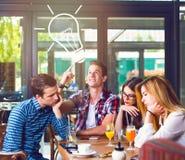 Giovane con un'idea, sedentesi con i suoi amici Fotografie Stock Libere da Diritti