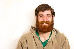 Giovane con una barba rossa che sorride sopra la macchina fotografica immagini stock libere da diritti