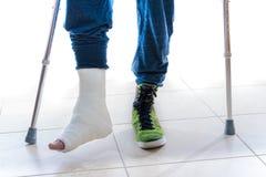 Giovane con una caviglia rotta e una colata della gamba Fotografie Stock