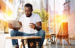 Giovane concentrato che sembra serio mentre sedendosi con la sua compressa Fotografie Stock