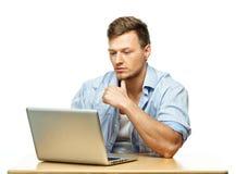 Giovane concentrato dietro il computer portatile Immagini Stock