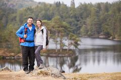 Giovane condizione adulta delle coppie su una roccia accanto ad un lago in campagna, sorridente alla macchina fotografica, integr immagini stock