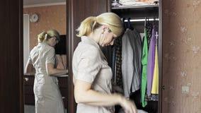 Giovane condizione bionda della donna davanti ad un guardaroba aperto a casa e sbottonare il suo vestito domestico per cambiare i archivi video