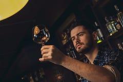 Giovane condizione del barista al contatore della barra che controlla pulizia di vetro immagine stock libera da diritti