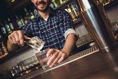 Giovane condizione del barista al contatore della barra che mette cubetto di ghiaccio in allegro di vetro immagini stock libere da diritti