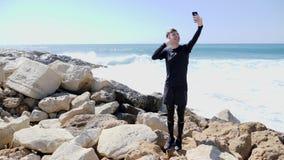Giovane condizione felice allegra esile dell'uomo sulla spiaggia rocciosa che prende i selfies e che mostra i pollici sull'acqua  stock footage