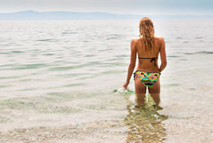 Giovane condizione femminile nel mare che tocca la superficie, giusta vista Fotografie Stock Libere da Diritti