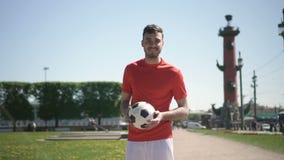 Giovane condizione maschio del giocatore di football americano, mettente palla da corpo a corpo e sorridente con un parco piacevo archivi video
