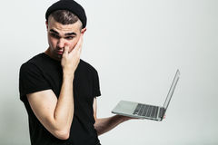 Giovane confuso con il computer portatile in studio immagini stock libere da diritti