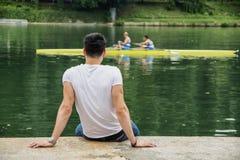 Giovane contemplativo che si siede accanto al fiume Fotografia Stock