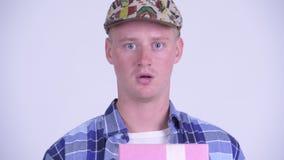 Giovane contenitore di regalo felice di apertura dell'uomo dei pantaloni a vita bassa e guardare sorpreso video d archivio