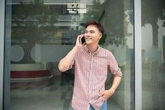 Giovane conversazione dell'uomo d'affari al cellulare in ufficio immagine stock libera da diritti