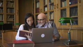 Giovane conversazione di professore del biologo e dello studente, sedentesi alla tavola con il computer portatile in biblioteca video d archivio