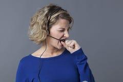 Giovane conversazione professionale femminile sottolineata con una cuffia avricolare con nervosismo fotografia stock