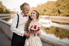 Giovane coppia sposata che cammina lungo la sponda del fiume immagini stock