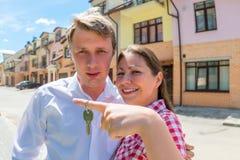 Giovane coppia sposata che mostra le chiavi dalla nuova casa immagine stock libera da diritti