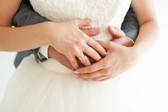 Giovane coppia sposata che si tiene per mano con gli anelli su fondo bianco, giorno delle nozze di cerimonia immagine stock libera da diritti