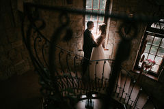 Giovane coppia sposata che sta faccia a faccia alle scale ed a tenersi per mano fotografia stock libera da diritti