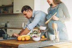Giovane coppia sposata in cucina L'uomo sta la tavola vicina ed utilizza il computer portatile, moglie incinta sta stando accanto fotografia stock libera da diritti