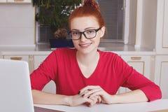 Giovane in copywriter femminile esperto della testarossa con pelle freckled, indossa gli occhiali quadrati, lavora al computer po fotografie stock