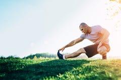 Giovane corridore atletico che fa allungando esercizio, preparante per l'allenamento nel parco Tramonto Immagini Stock Libere da Diritti