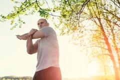 Giovane corridore atletico che fa allungando esercizio, preparante per l'allenamento nel parco Tramonto Fotografia Stock Libera da Diritti