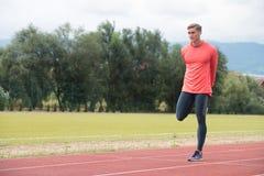 Giovane corridore dell'uomo di forma fisica che allunga le gambe prima del funzionamento Fotografie Stock