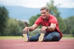 Giovane corridore dell'uomo di forma fisica che allunga le gambe prima del funzionamento Immagini Stock Libere da Diritti