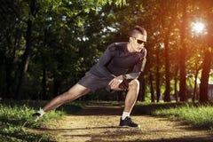 Giovane corridore dell'uomo di forma fisica che allunga le gambe prima del funzionamento Fotografie Stock Libere da Diritti